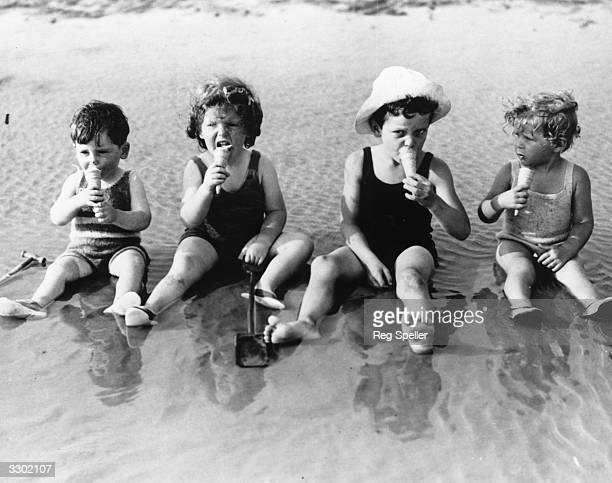 A group of young children sit in the shallows as they enjoy an icecream at Littlehampton