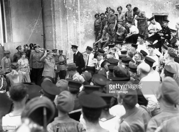 British politician and Prime Minister Winston Churchill giving the victory sign to men of the British Army and Navy behind Churchill is his Russian...