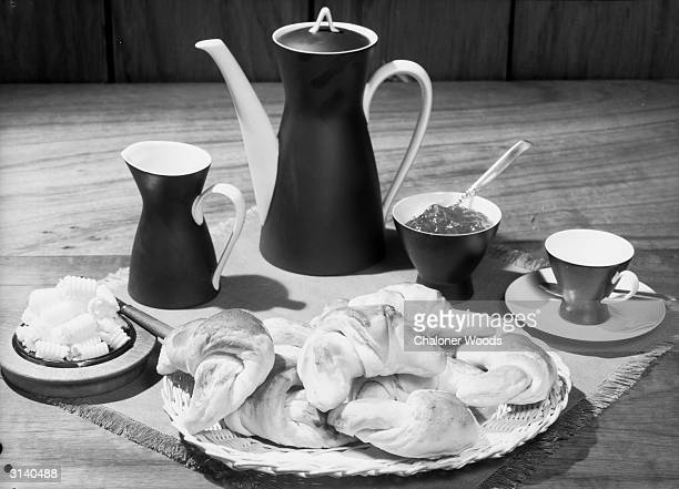 A breakfast tray laden with croissants butter and jam and coffee in an elegant coffee pot