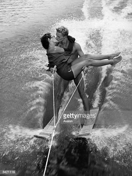 Well-balanced couple enjoying a kiss while water-skiing.