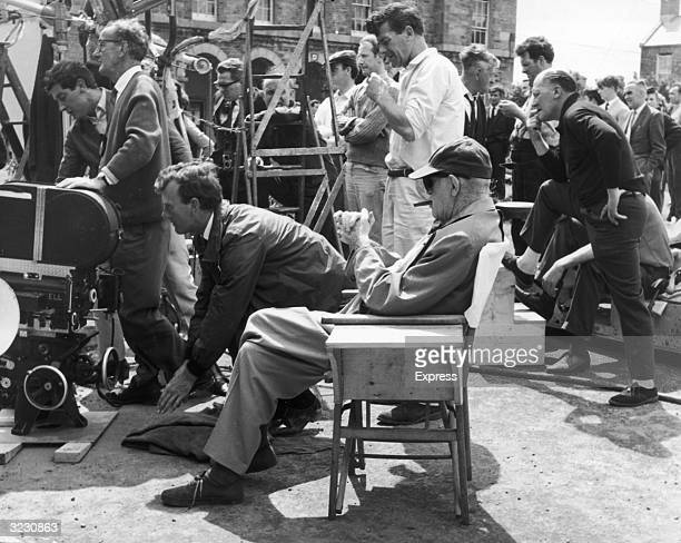 American film director John Ford wearing a baseball cap sunglasses and smoking a cigar sits in a director's chair amidst his crew on location for the...