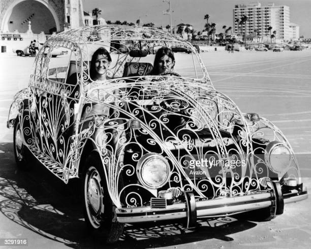 Two women sit in their Volkswagen Beetle car which has been customized with a wroughtiron body at Daytona Beach Florida