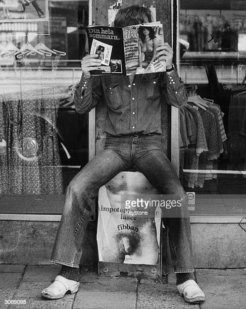 A Swedish man wearing clogs and reading a pornographic magazine