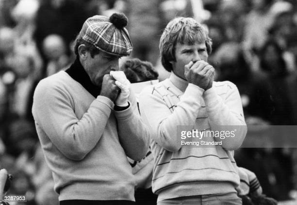 American golfer Ben Crenshaw and Australian golfer Graham Marsh blowing their hands to try to keep warm before driving off in the British Open at...