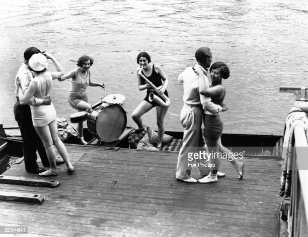 Two couples dancing to jazz on the riverside played on a punt by two women dressed in swimming costumes