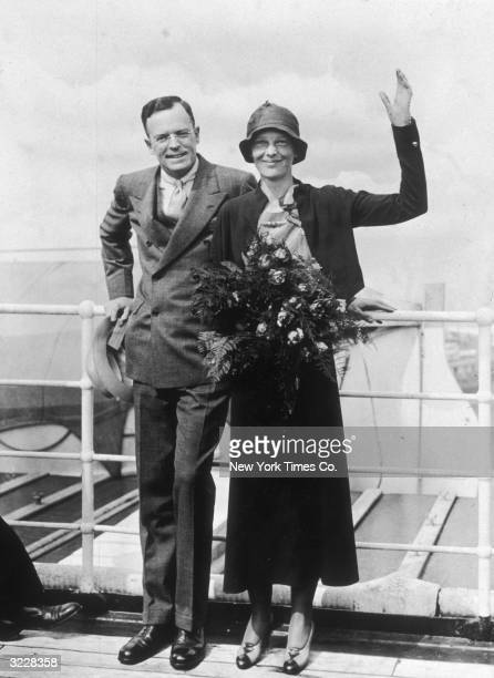 Full-length image of aviator Amelia Earhart and her husband, publisher George Palmer Putnam, waving as they return from Europe aboard the S.S. 'Ile...
