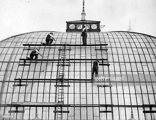 Men carry out restoration and maintenance work on a huge section of glass panelling on the roof of Alexandra Palace London
