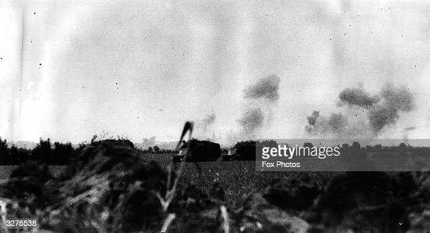 A convoy of army lorries makes its way through an area of heavy bombardment during the final days of the siege of Dunkirk