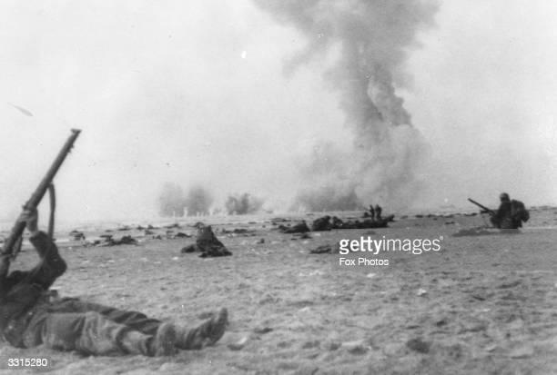 Soldiers of the British Epeditionary Force lie on their backs on the beach at Dunkirk to shoot with their rifles at enemy aircraft which are bombing...
