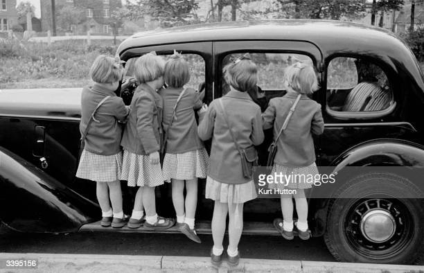 The Good quadruplets fiveyearold Jennifer Bridget Elizabeth and Frances with their big sister sevenyearold Susan standing on a car's runningboard...