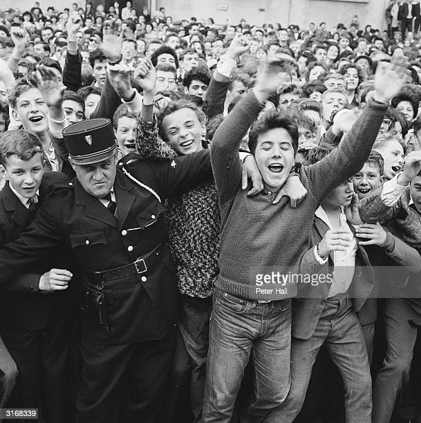 A French policeman has trouble controlling a crowd of French fans who are in Calais to greet the arrival from Gravesend of a specially chartered...
