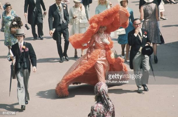 At Ascot races Mrs Gertrude Shilling in an apricot coloured, feather trimmed out fit, which is completed by an enormous, matching, cartwheel hat.