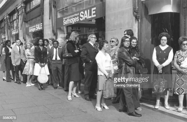 Shoppers queuing up outside Selfridges in London during a summer sale.