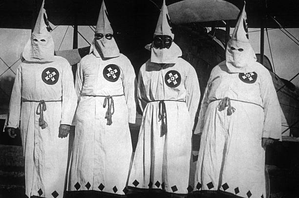 Members of the white supremacist movement, the Ku Klux Klan standing by an aeroplane, out of which they dropped publicity leaflets over Washington DC.