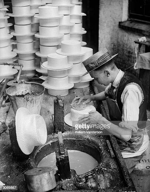Hatter at Messrs Olney's in Luton, Bedfordshire covering straw boaters with gelatine to harden them after they have been moulded into shape.