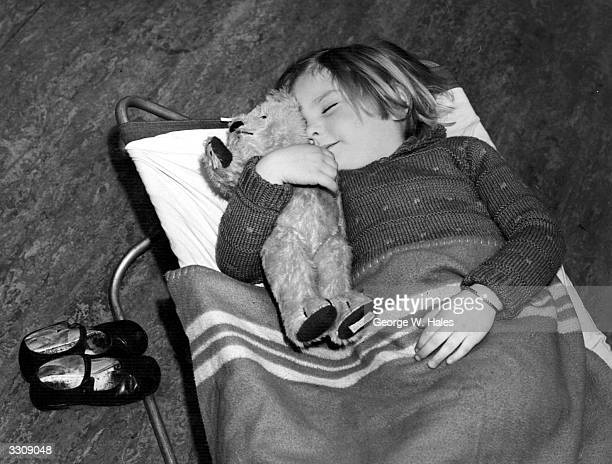 A young pupil clutching her teddy bear having a midday nap at her school