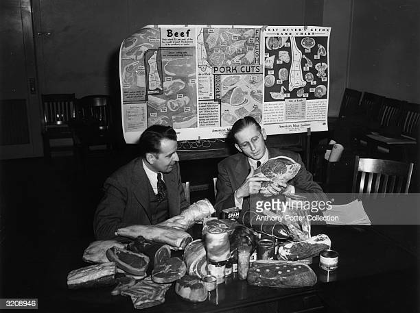 Assistant Director of OPA's Food Rationing Division, J.H. Westing and Leon Bosch, Head of Point Control Development, use papier-mache meat cuts to...