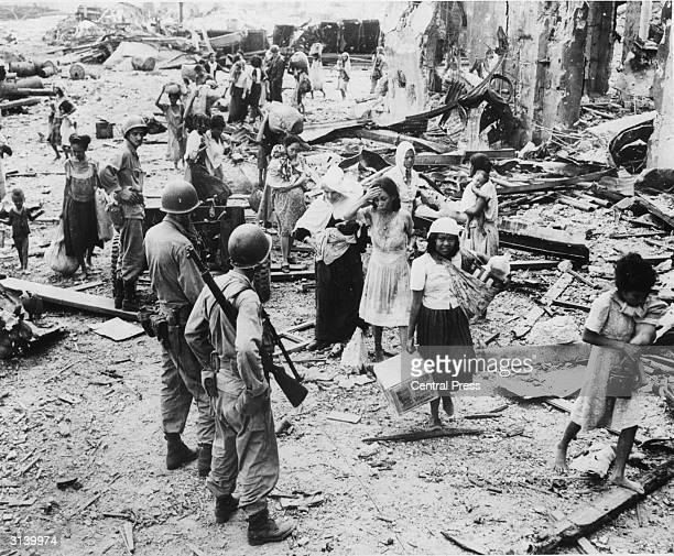 American soldiers watching as refugees pick their way through the debris of North Manila after safely arriving in the American held part of the city...