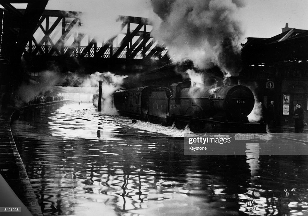 A train leaving Nottingham station starts a 'bow wave' that nearly swamps a platform during floods caused by the River Trent overflowing.