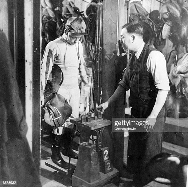 Jump jockey Raymond Cane second jockey for Jack Fawcus's stable in Yorkshire watches a valet weigh him prior to an official weighin by the Clerk of...