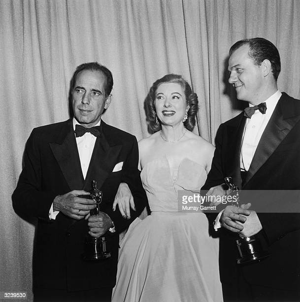 EXCLUSIVE British actor Greer Garson stands arminarm between Oscar winners Humphrey Bogart and Karl Malden backstage at the Academy Awards RKO...