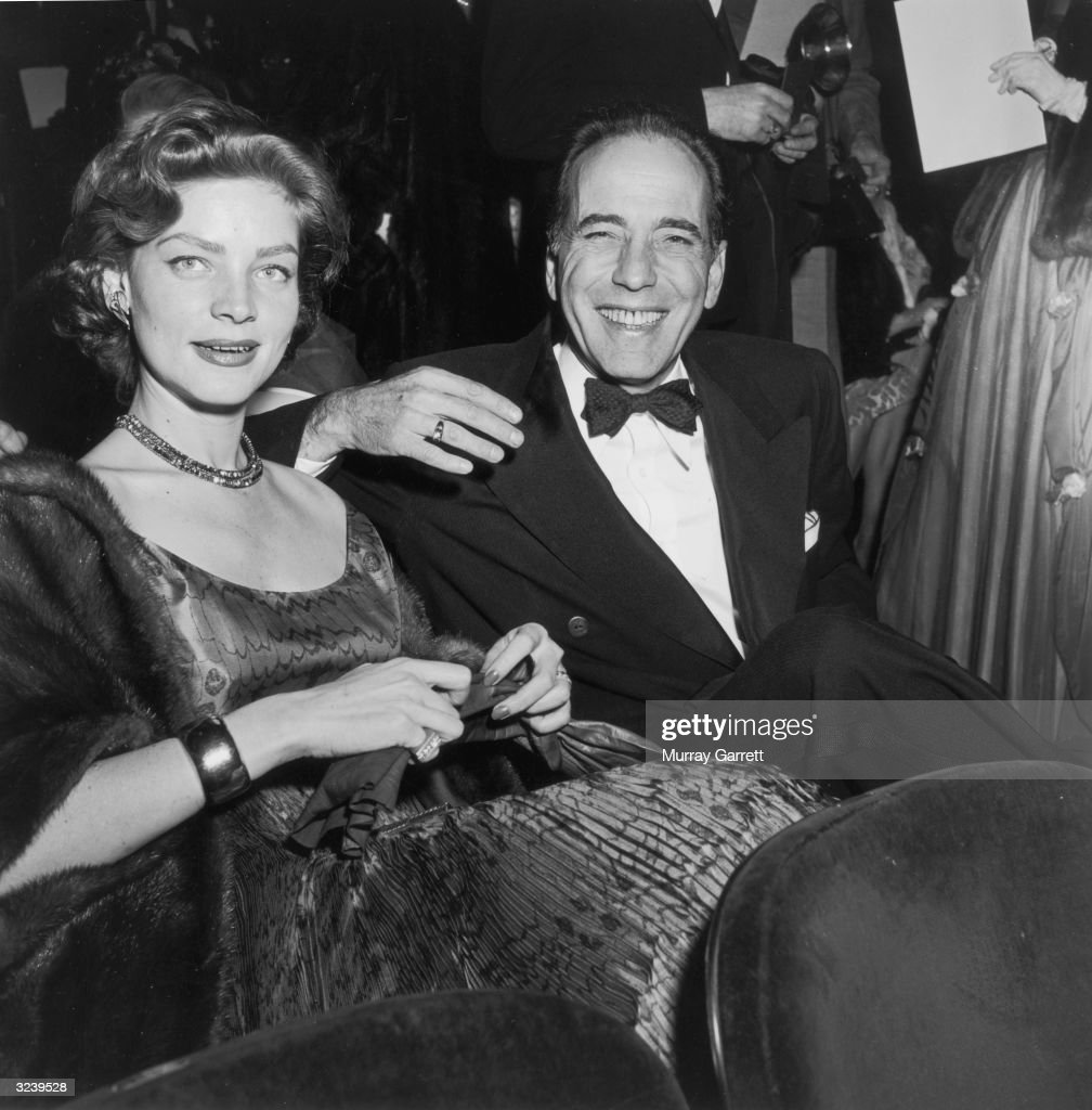 Married American actors Lauren Bacall and Humphrey Bogart (1899 - 1957) smile while seated in formal evening wear at the Academy Awards, RKO Pantages Theater, Los Angeles, California. Bogart won for Best Actor in director John Huston's film, 'The African Queen.'