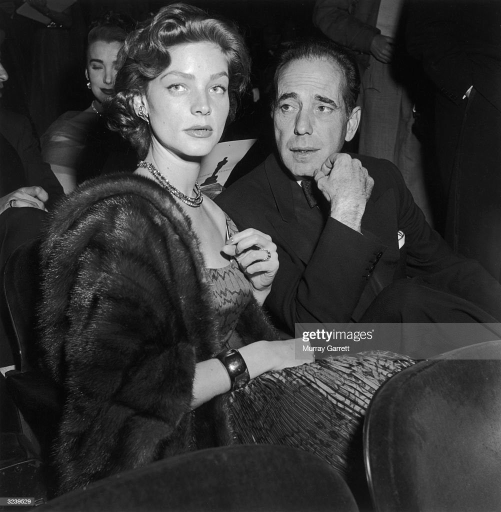 Married American actors Lauren Bacall and Humphrey Bogart (1899 - 1957) wear formal evening clothes while seated at the Academy Awards, RKO Pantages Theater, Los Angeles, California. Bogart won for Best Actor in director John Huston's film, 'The African Queen.'