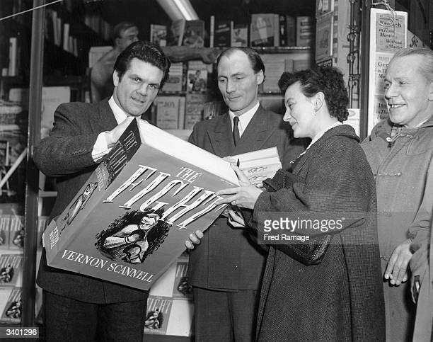 British boxer Freddie Mills signing an oversized copy of writer Vernon Scannell's first novel 'The Fight' outside Panzetta's bookshop in London's...