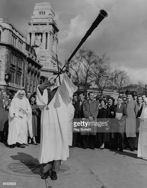 The Herald of the Ancient Order of Druids blowing a long horn to mark the Vernal Equinox of the Sun at Tower Hill in London