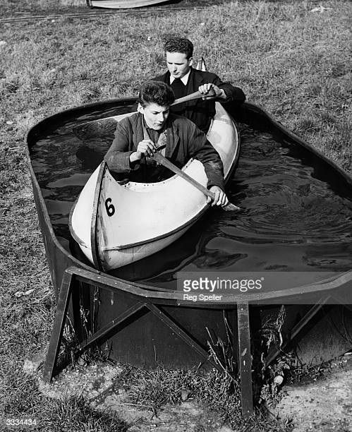 Tony Millis and Ronald Bullman testing a fibre glass canoe in the testing tank at the Peter Pan Pool Catford where they are being made for the...