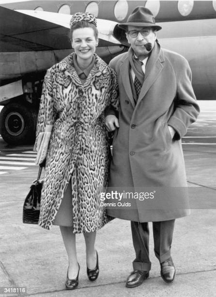 Georges Simenon, famous creator of the fictional French detective 'Inspector Maigret', arrives at London Airport with his wife Denise.