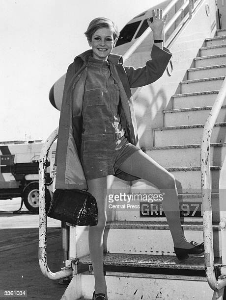 British fashion model Twiggy wearing green shorts and blue tights under an orange coat waves from the aircraft steps at London Airport on her way to...