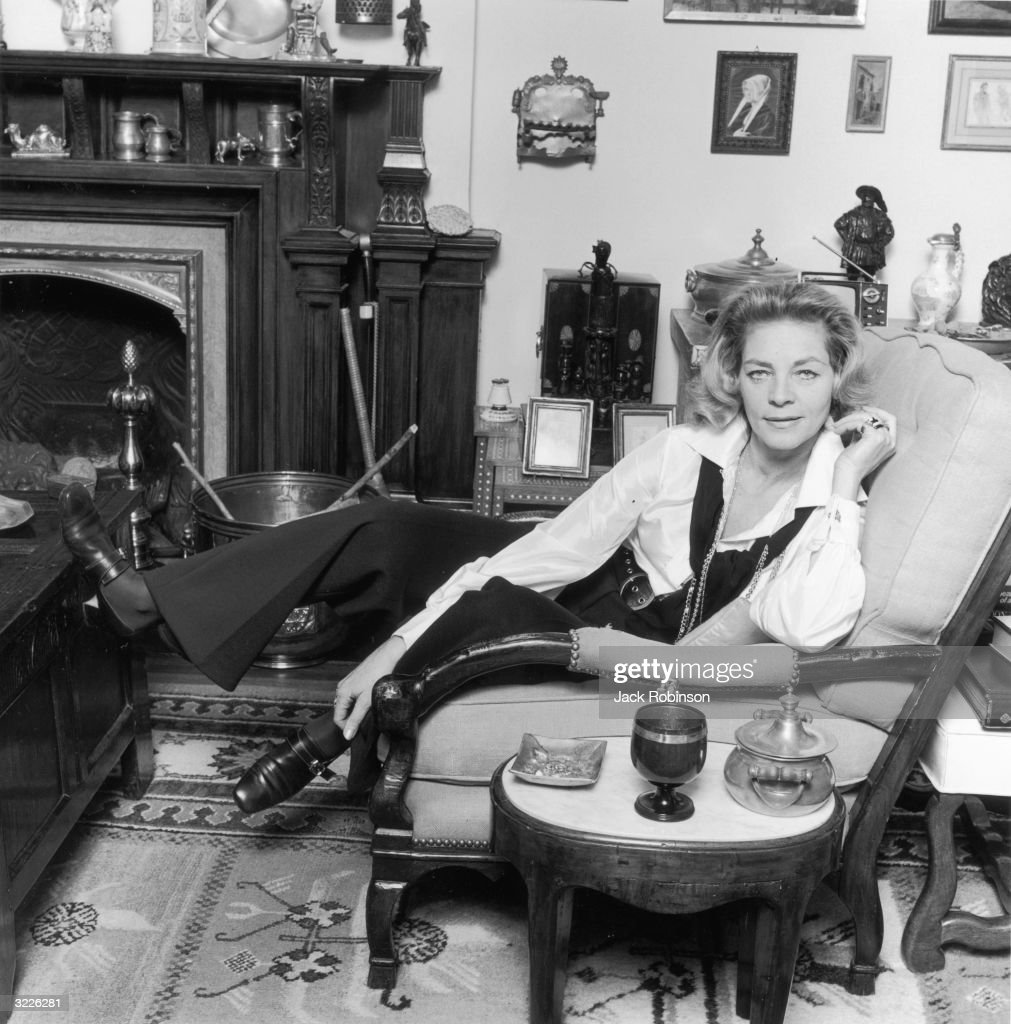Portrait of American actor Lauren Bacall sitting in an armchair with one leg propped on a table, at her home. There is a fireplace behind her.
