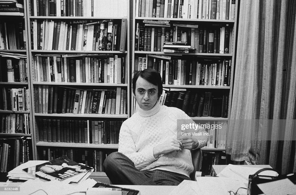 American astronomer and author Carl Sagan (1934 - 1996) sitting at a desk in front of bookcases at Cornell University, Ithaca, New York. He is wearing a turtleneck sweater and pinstriped pants.