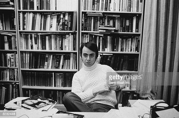 American astronomer and author Carl Sagan sitting at a desk in front of bookcases at Cornell University Ithaca New York He is wearing a turtleneck...