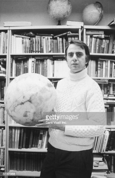 Portrait of American astronomer and author Carl Sagan holding a globe in front of bookcases at Cornell University Ithaca New York He is wearing a...