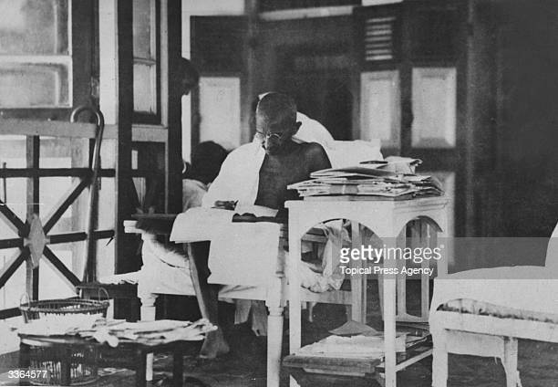 Indian statesman Mahatma Gandhi reading his correspondance whilst living in seclusion after being released from prison