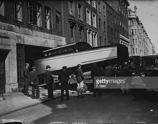 Cabin cruiser, destined for Sunbury-on-Thames, at its 'launch' from a motor-showroom onto a lorry, at Great Portland Street, London.