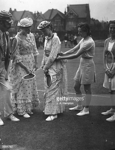 British tennis player Kay Stammers adjusts the dress of one of the players in a mixed doubles exhibition match to be played in 1879 costume as part...
