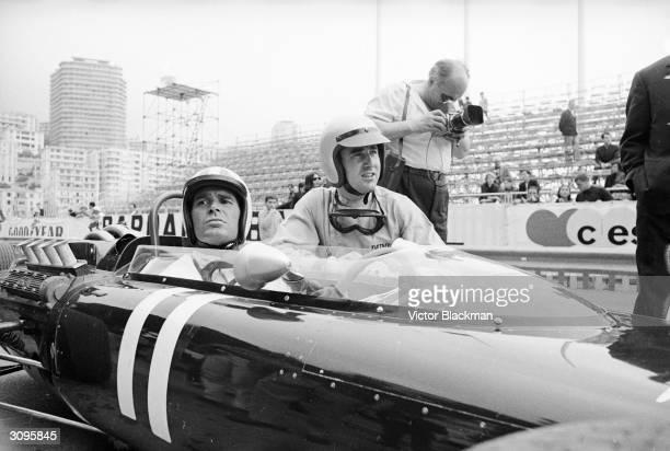 American actor James Garner in a racing car at the Monaco Grand Prix. Kneeling beside him is Ferrari driver Lorenzo Bandini.