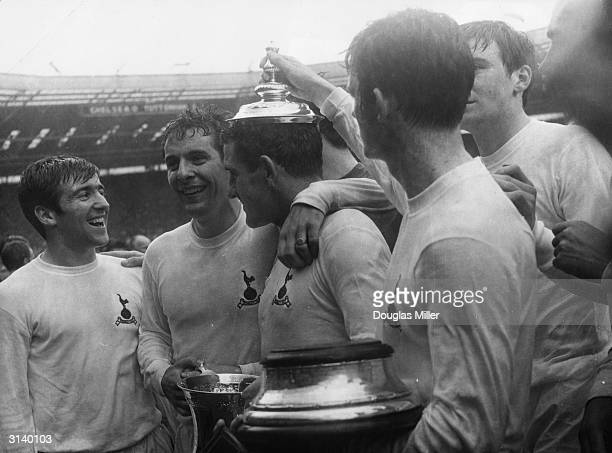Dave Mackay captain of Tottenham Hotspur football club has the lid of the FA Cup playfully put on his head by teammate Jimmy Robertson watched by...