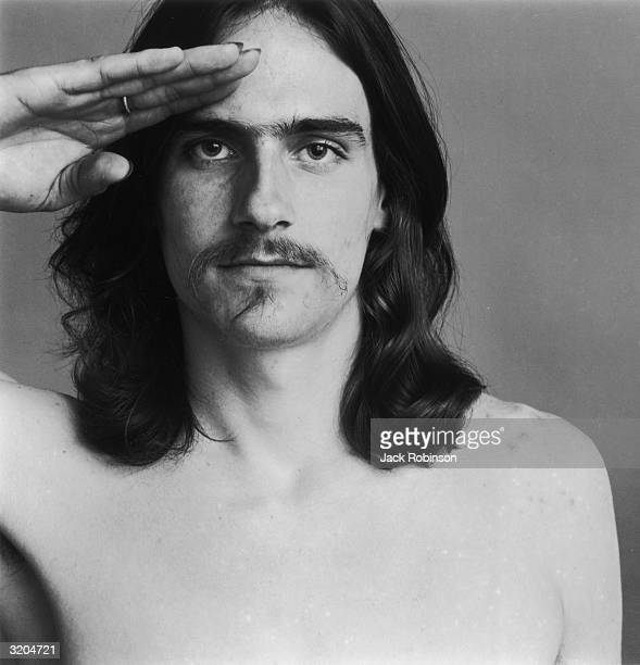 Headshot portrait of American folk musician James Taylor saluting