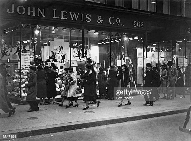 Passersby outside John Lewis and Co's department store in Oxford Street London where there is a window display for Christmas gifts