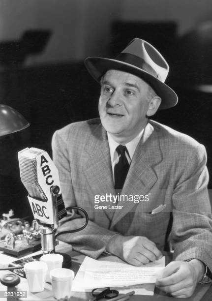 EXCLUSIVE American journalist Walter Winchell holds pages of his copy while speaking into an ABC microphone