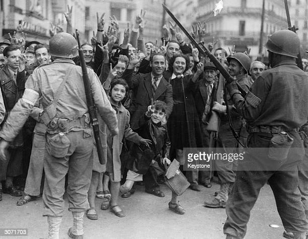 American soldiers keeping order whilst the Algiers crowds cheer the Allies and jeer the Italians who are being transported through the town on their...