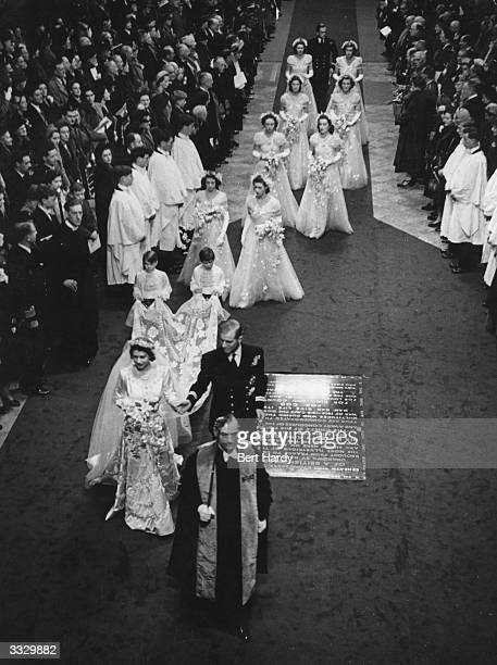 Princess Elizabeth and Prince Philip Duke of Edinburgh in the aisle of Westminster Abbey London on their wedding day followed by their bridesmaids...