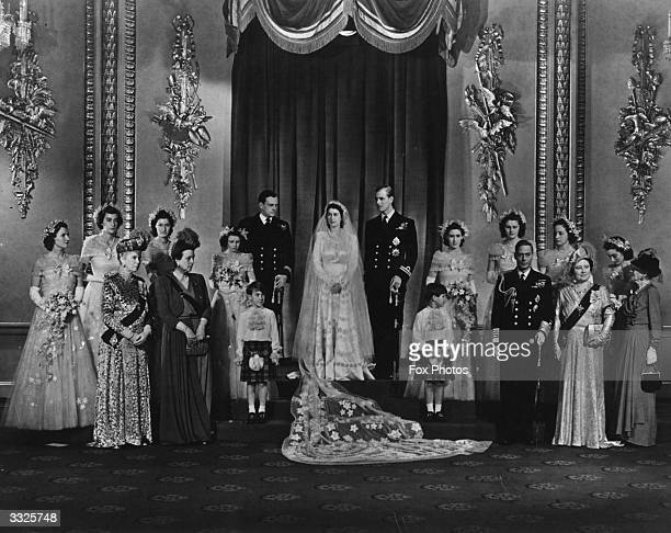 Queen Elizabeth and Prince Philip Duke of Edinburgh on their wedding day surrounded by members of the Royal Family The guests include Queen Mary...