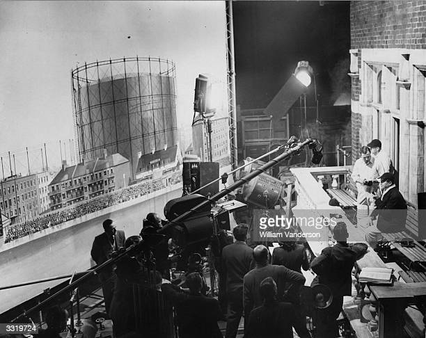 British cricketer Len Hutton and actor Jack Warner on a film set of the balcony at the Oval in Pinewood Studio's during filming of Terrence...