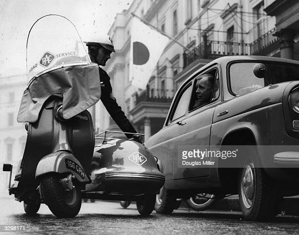 Royal Automobile Club patrolman Alan Otter stops to talk to a motorist in a Ford 100E Anglia whilst driving a scooter with sidecar through London's...