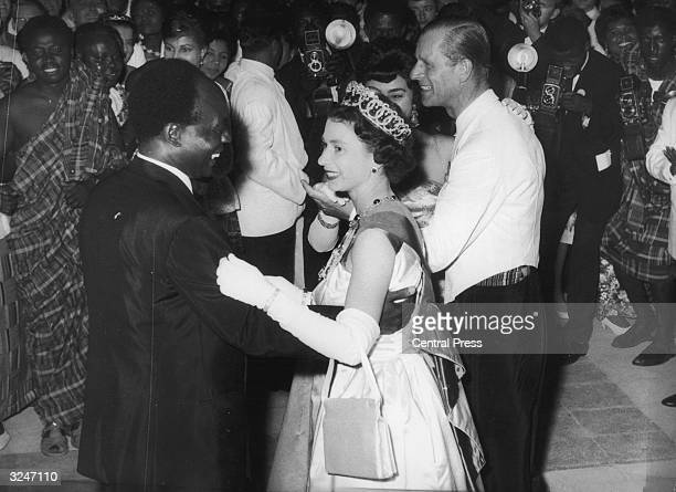 Queen Elizabeth II dances with Ghanaian president Kwame Nkrumah at a farewell ball held at State House, Accra. They, and the Duke of Edinburgh, are...
